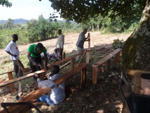 Men building benches in a rural property - they started without a building.