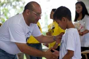 Alex greets a child after presenting an award at a VBS ministry of a White Fields church.