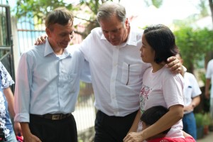 Director Steve Wheeler prays with a pastor and his wife on a visit to their church.